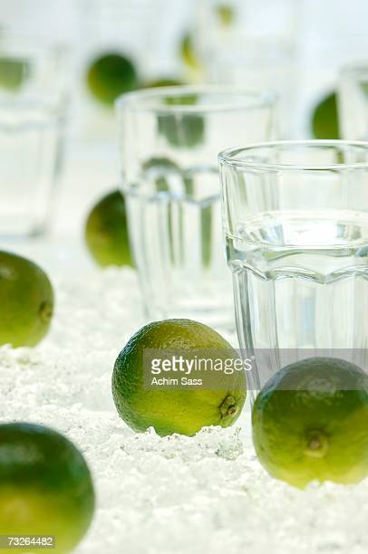Lime fruits and water glass on crushed ice, close-up