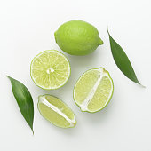 some fresh limes with leaves on a white background
