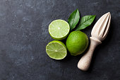 Limes and juicer on stone background. Top view with copy space