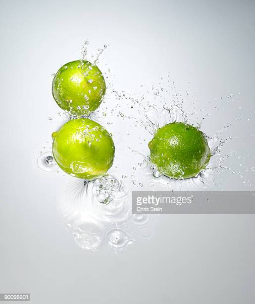 Limes splashing in to water