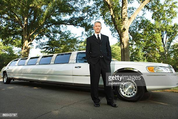 Limousine chauffeur standing in suit