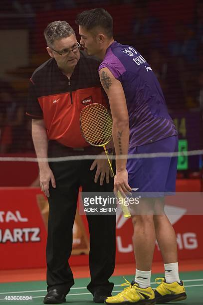 Lin Dan of China speaks to an official for a technical problem during his men's singles qualifying match against Sattawat Pongnairat of the US at the...