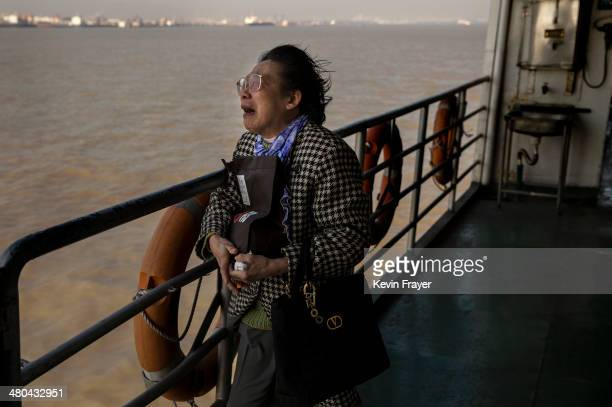 Lin Hui Zhen 76 years weeps as she clutches the small bag carrying the ashes of her late husband Fu Yao Ming 80 years during a sea burial organized...