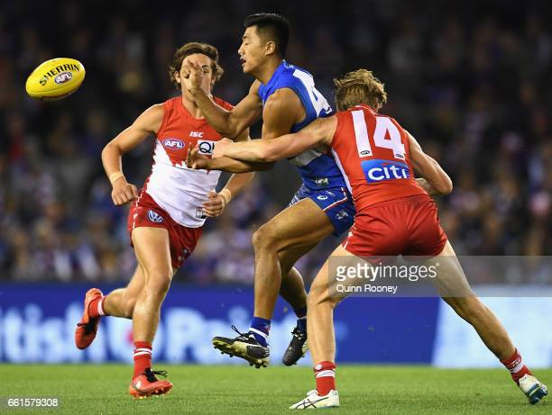 Lin Jong of the Bulldogs handballs whilst being tackled by Callum Mills of the Swans during the round two AFL match between the Western Bulldogs and...