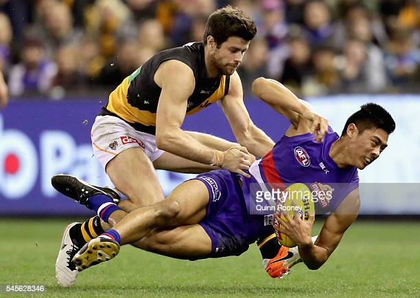 Lin Jong of the Bulldogs is tackled by Trent Cotchin of the Tigers during the round 16 AFL match between the Western Bulldogs and the Richmond Tigers...