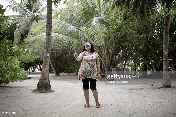 Lin Lillin Xia who travelled to the Maldives from Chengdu with her family for a short vacation takes a selfie while walking along the beach on...