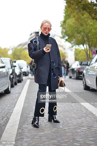 Lin Xiao poses wearing Jacquemus coat and pants and Prada shoes before the Miu Miu show at the Palais de Iena during Paris Fashion Week SS16 on...