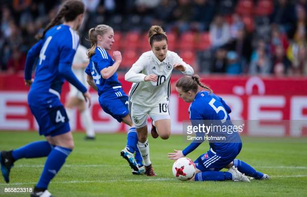 Lina Magull of Germany is challenged by Susanna Maria Hansen and Anna Sofia Sevdal of Faroe Islands during the 2019 FIFA Women's World Championship...
