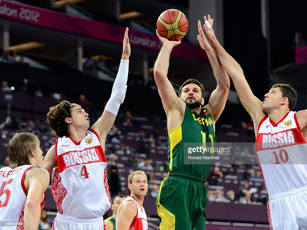 Linas Kleiza #11 of Lithuania goes up for a shot between Alexey Shved #4 and Victor Khryapa #10 of Russia in the first half during the Men's Basketball quaterfinal game on Day 12 of the London 2012 Olympic Games at North Greenwich Arena on August 8, 2012 in London, England.