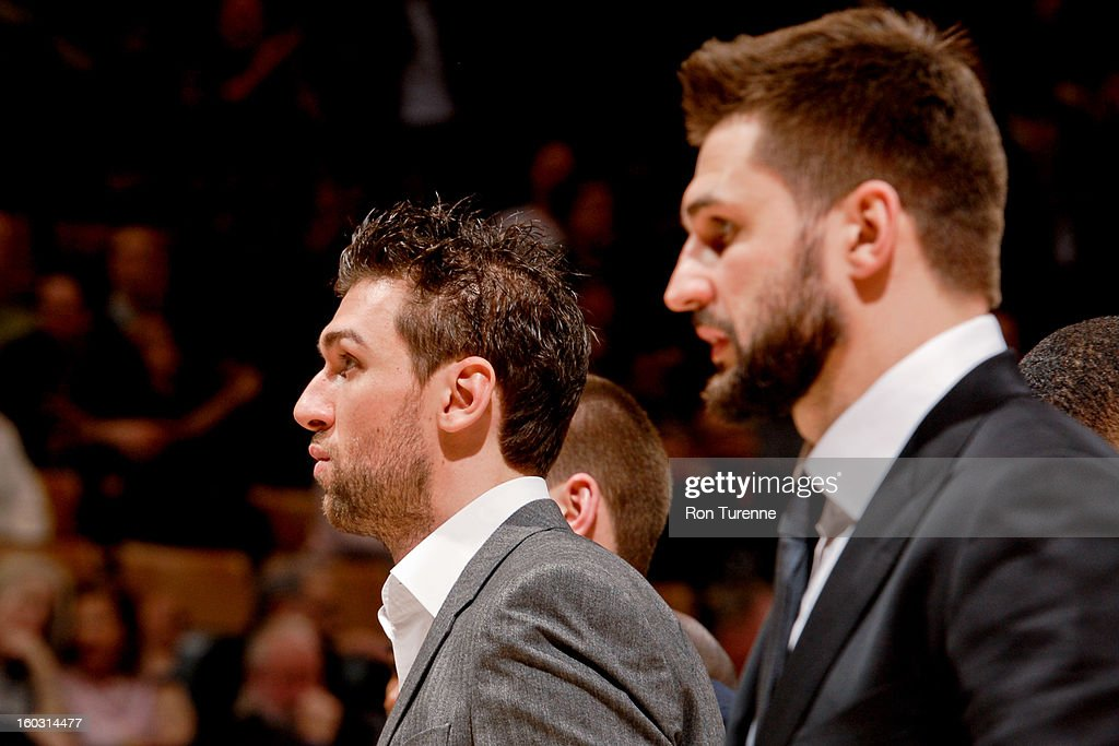 Linas Kleiza #11, right, and Andrea Bargnani #7 of the Toronto Raptors look on in street clothes during a game against the Golden State Warriors on January 28, 2013 at the Air Canada Centre in Toronto, Ontario, Canada.