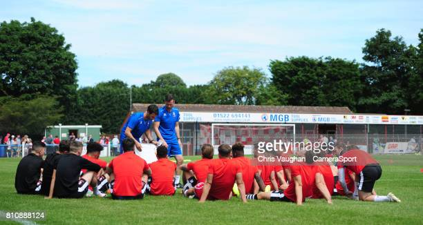 Lincoln City manager Danny Cowley and Lincoln City's assistant manager Nicky Cowley deliver a teamtalk on the pitch prior to the preseason friendly...