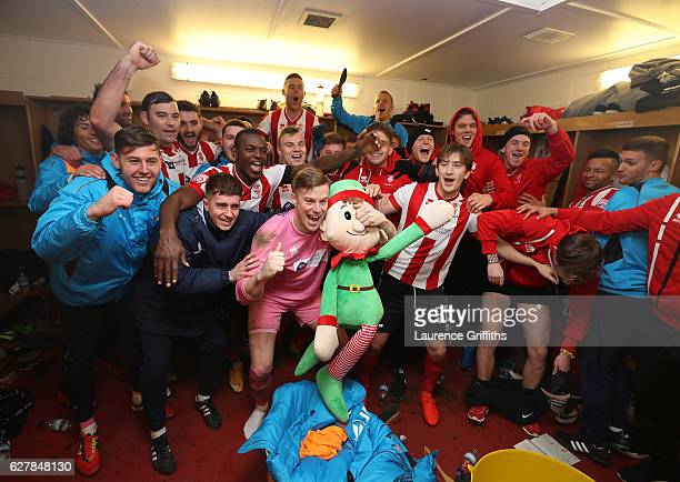 Lincoln City players celebrate in the dressing room after the Emirates FA Cup Second Round match between Lincoln City and Oldham Athletic at Sincil...