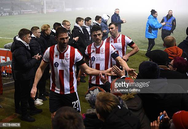 Lincoln City players celebrate with the fans as they walk into the dressing rooms after the Emirates FA Cup Second Round match between Lincoln City...