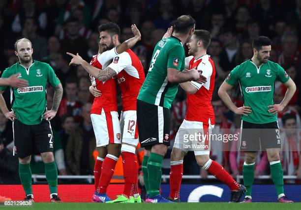 Lincoln City players look dejected Theo Walcott of Arsenal celebrates with team mate Olivier Giroud of Arsenal as he scores the first goal during The...