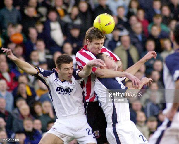Lincoln City's Ben Futcher wins an aerial battle against Hull City's Steve Burton and Damien Delaney during their Nationwide Division Three match at...