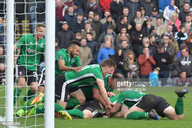 Lincoln City's English defender Sean Raggett celebrates with teammates after scoring during the English FA Cup fifth round football match between...