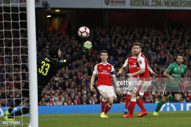 Lincoln City's English midfielder Nathan Arnold watches Arsenal's Czech goalkeeper Petr Cech save his shot during the English FA cup quarter final...