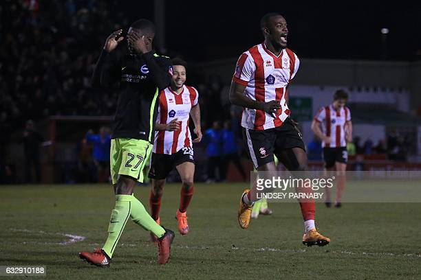 Lincoln City's Englishborn Jamaican striker Theo Robinson runs past Brighton's Canadianborn English Fikayo Tomori as he celebrates scoring his team's...