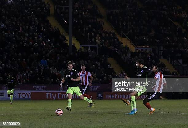 Lincoln City's Englishborn Jamaican striker Theo Robinson shoots past Brighton's English defender Connor Goldson to score his team's third goal...