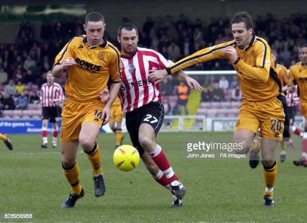 Lincoln City's Gary Fletcher comes under pressure from Hull's Damien Delaney and Lee Marshall during the Nationwide Division Three match at Sincil...