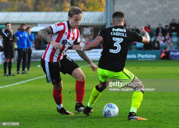 Lincoln City's Jordan MaguireDrew vies for possession with Cambridge United's Jake Carroll during the Sky Bet League Two match between Lincoln City...