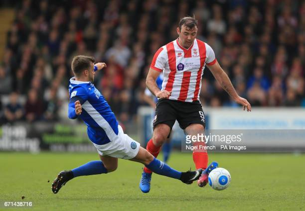 Lincoln City's Matt Rhead and Macclesfield Town's Andy Halls battle for the ball during the Vanarama National League match at Sincil Bank Lincoln