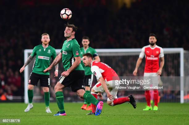 Lincoln City's Matt Rhead heads forward under pressure from Arsenal's Aaron Ramsey during the Emirates FA Cup QuarterFinal match between Arsenal and...