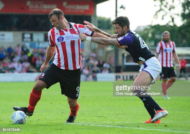 Lincoln City's Matt Rhead shields the ball from Luton Town's Alan Sheehan during the Sky Bet League Two match between Lincoln City and Luton Town at...
