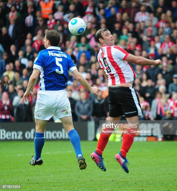 Lincoln City's Matt Rhead vies for possession with Macclesfield Town's George Pilkington during the Vanarama National League match between Lincoln...