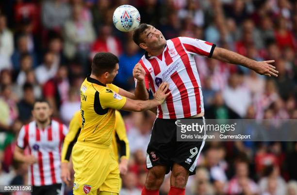 Lincoln City's Matt Rhead vies for possession with Morecambe's Alex Kenyon during the Sky Bet League Two match between Lincoln City and Morecambe at...