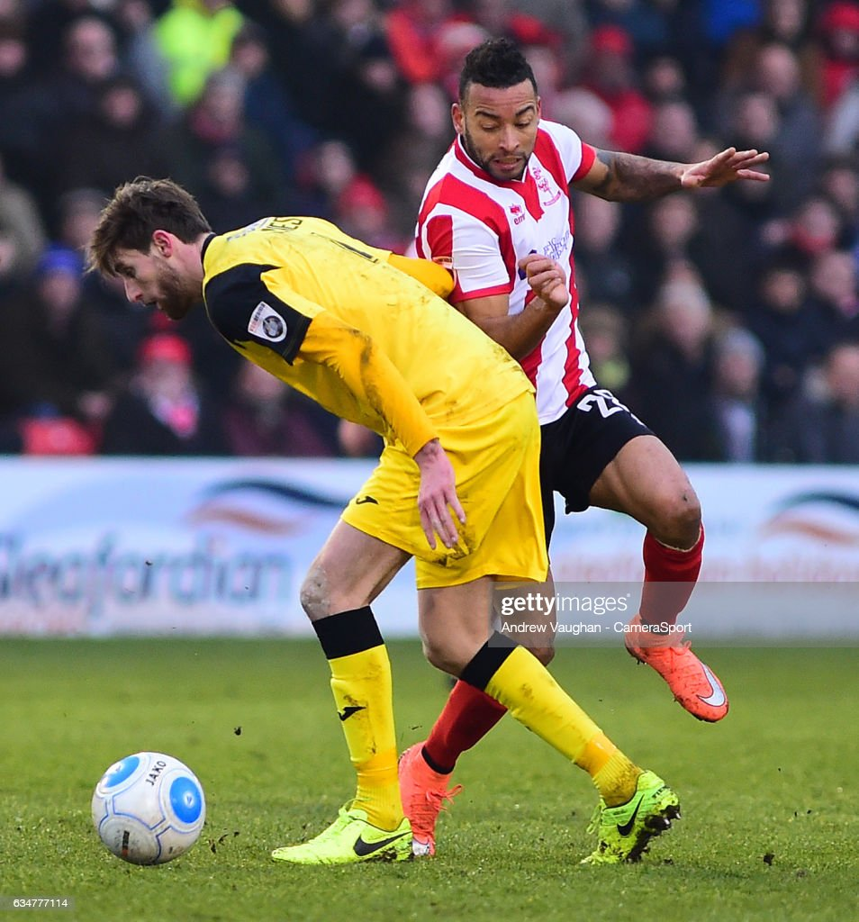 Lincoln City's Nathan Arnold vies for possession with Woking's Joe Jones during the Vanarama National League match between Lincoln City and Woking at Sincil Bank Stadium on February 11, 2017 in Lincoln, England.