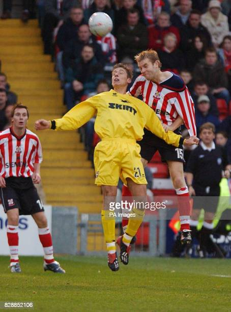 Lincoln defender Simon Weaver gets his shirt tugged by Brighton's Chris McPhee as they jump for the ball during their FA Cup 1st round match at...