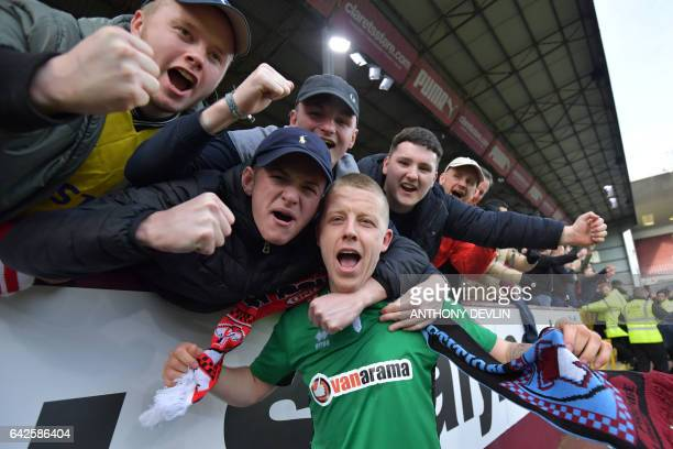 Lincoln fans celebrate with Lincoln City's English midfielder Terry Hawkridge after winning the English FA Cup fifth round football match between...