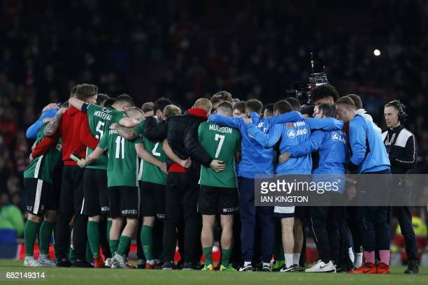 Lincoln players and staff form a group huddle on the pitch after the English FA cup quarter final football match between Arsenal and Lincoln City at...