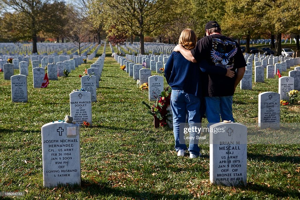 Linda and Gene Lamie, of Georgia, stand before the grave of their son, Sgt. Gene L. Lamie, on Veteran's Day at Arlington National Cemetery on November 11, 2012 in Arlington, Virginia. Sgt. Lamie was killed during Operation Iraqi Freedom in 2007 at the age of 25. Numerous events are under across the country to honor the nation's current and former service members.