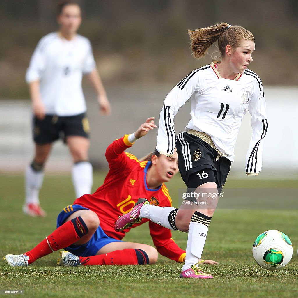 Linda Dallmann of Germany is challenged by Virginia Torrecilla Reyes of Spain during the Women's UEFA U19 Euro Qualification match between U19 Germany and U19 Spain at Waldstadion in Viernheim on April 4, 2013 in Viernheim, Germany.