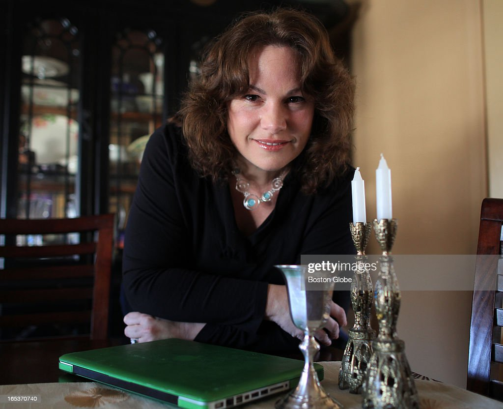 Linda Goodspeed will be using a laptop to include other family members during Passover Seder. There is a Kiddush Cup and Sabbath Candlesticks on the table, that will be used.