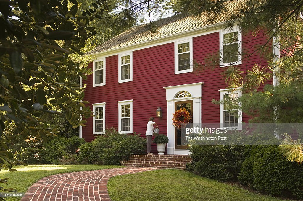 Linda Hobbins waters the mums on the front steps of her 18th century farmhouse in Potomac Maryland on August 29 2012