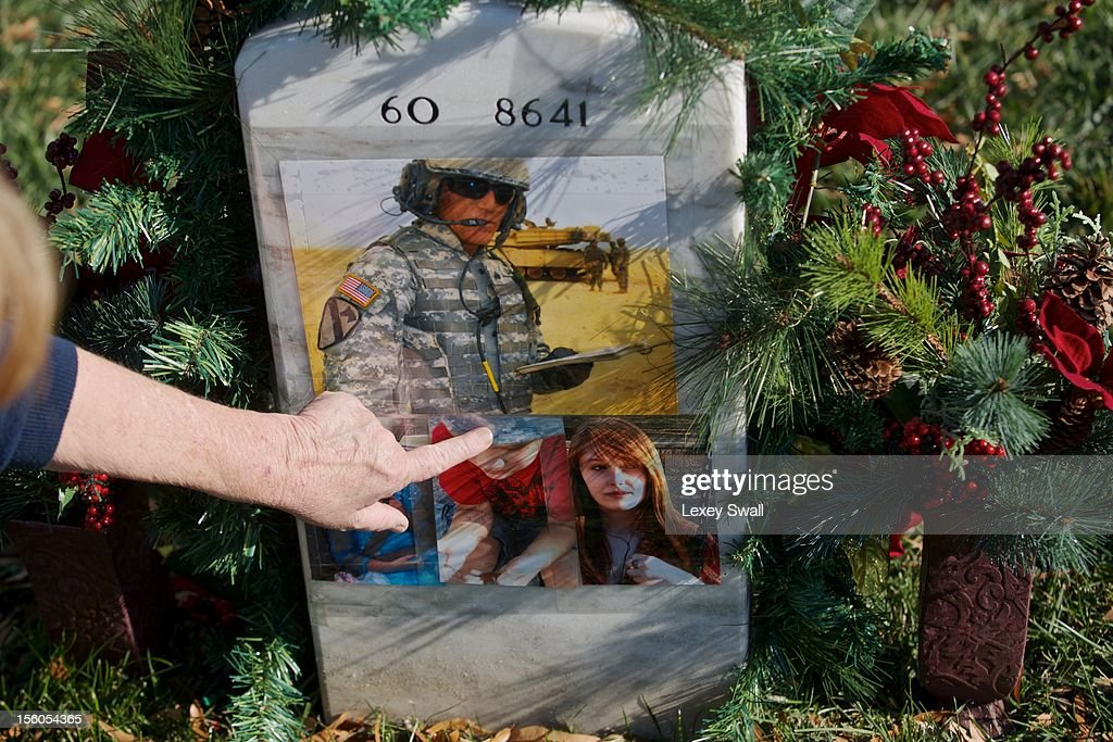 Linda Lamie, of Georgia, points to the grave of her son, Sgt. Gene L. Lamie, on Veteran's Day at Arlington National Cemetery on November 11, 2012 in Arlington, Virginia. Sgt. Lamie was killed during Operation Iraqi Freedom in 2007 at the age of 25. Numerous events are under across the country to honor the nation's current and former service members.