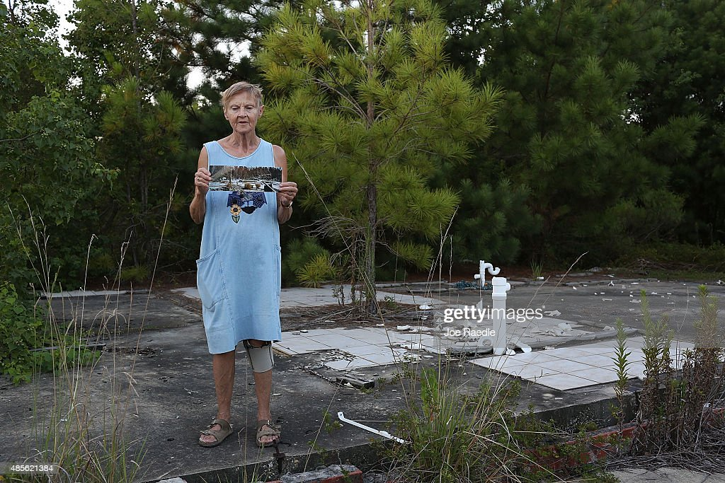 Linda McLain stands on the slab of her former home August 28 2015 in Waveland Mississippi McLain holds a photo that was taken by her son 10 days...