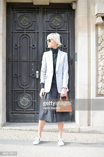 Linda Tol poses wearing LK Bennet jacket Uniqlo top Dries Van Noten pants Louis Vuitton bag and Adidas shoes on Day 5 of Paris Fashion Week...