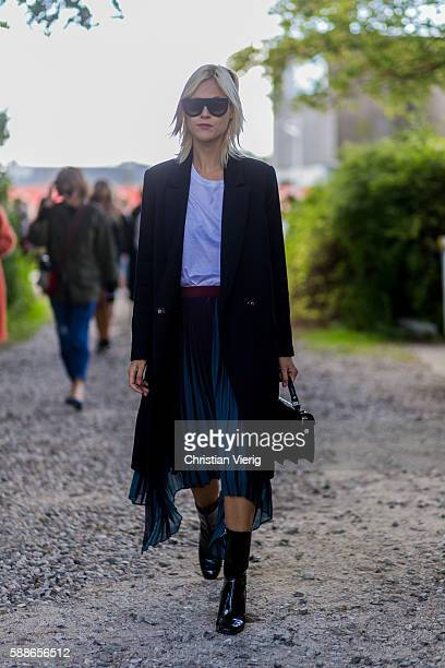 Linda Tol wearing a black coat white tshirt Dior boot and sunglasses soutside By Malene Birger during the second day of the Copenhagen Fashion Week...