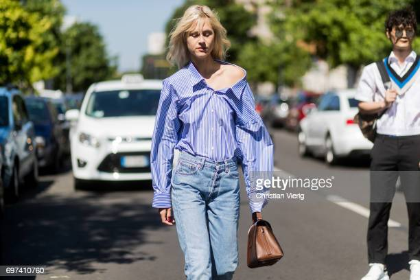 Linda Tol wearing a blue white striped button shirt denim jeans is seen outside MSGM during Milan Men's Fashion Week Spring/Summer 2018 on June 18...