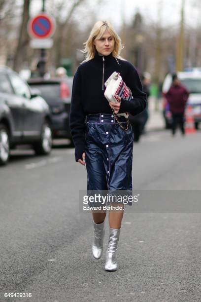 Linda Tol wears a black turtleneck top a blue leather skirt a colored clutch and silver boots outside the Chanel show during Paris Fashion Week...