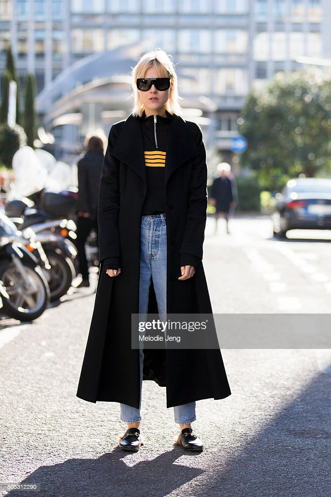 Linda Tol wears a Max Mara coat black and yellow Ganni zipstripe jacket highwaisted Levi's jeans Gucci Princetown leather slippers and Celine...