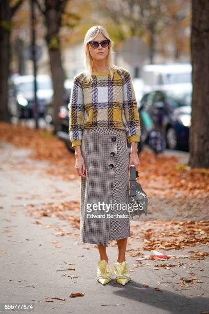 Linda Tol wears a tartan top a skirt yellow shoes a gray bag outside Issey Miyake during Paris Fashion Week Womenswear Spring/Summer 2018 on...