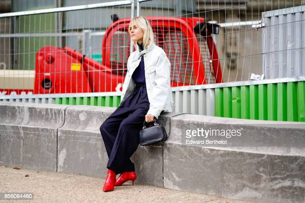 Linda Tol wears a white jacket a black dress red shoes outside Elie Saab during Paris Fashion Week Womenswear Spring/Summer 2018 on September 30 2017...
