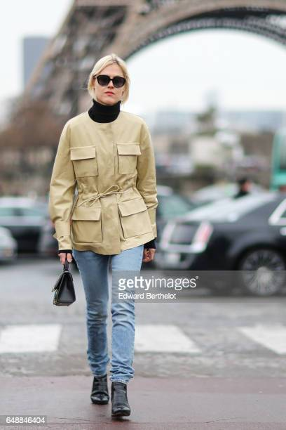 Linda Tol wears sunglasses a beige jacket a black turtleneck blue denim jeans a colored striped bag and black leather boots outside the Hermes show...