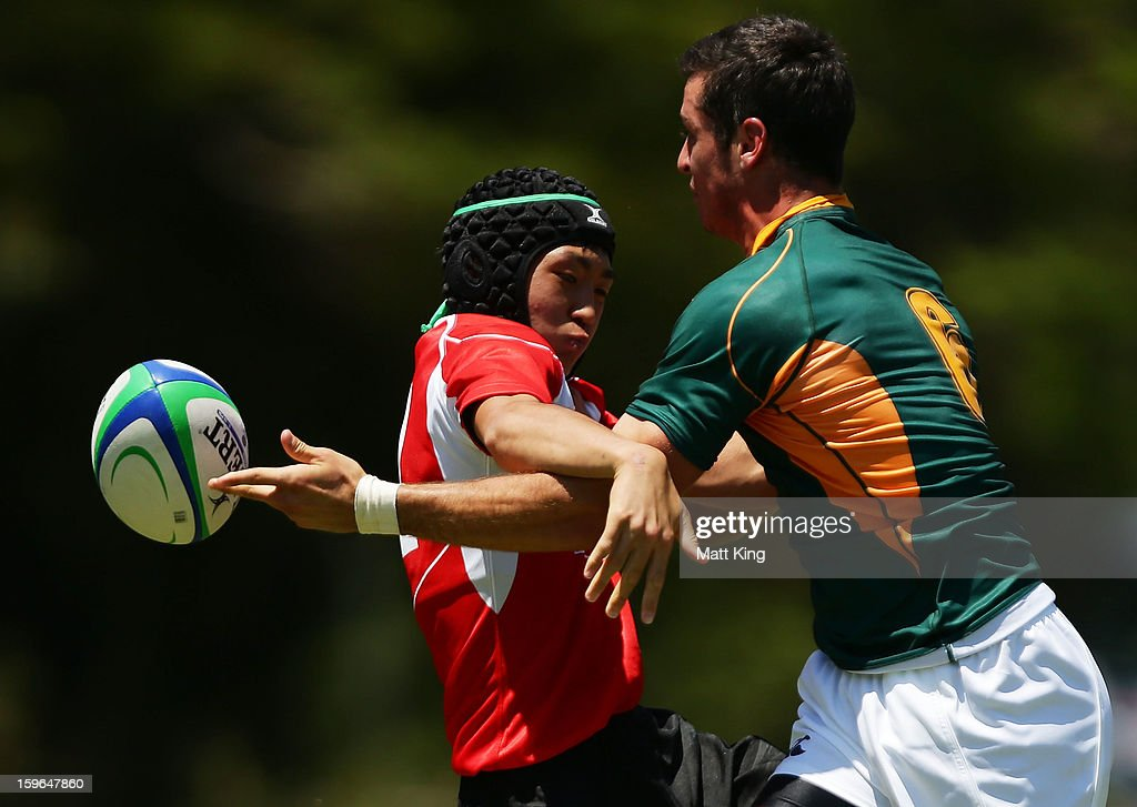 Linde Jurie (R) of South Africa gets a pass away past Miyazaki Eiya (L) of Japan in the Men's Rugby Sevens during day three of the Australian Youth Olympic Festival at St Ignatius College on January 18, 2013 in Sydney, Australia.