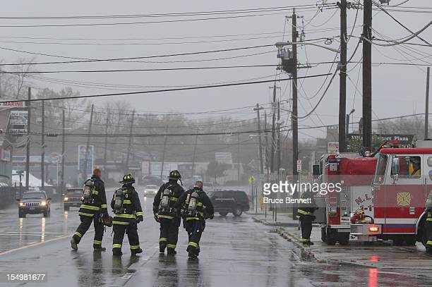 Lindenhurst firemen return to their truck after responding to a call as high tide rain and winds flood local streets on October 29 2012 in...